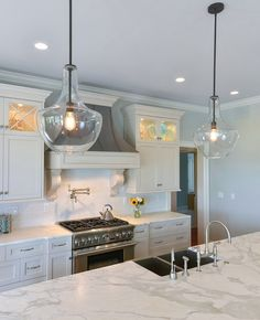 Simple elegant white kitchen + distressed gray hood + blue wall paint & gourd glass pendants