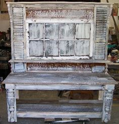 its all reclaimed parts....the legs are old turned legs cut in half, mounted on the main posts...,an old window makes the back....you can see spindles and corbels too....all this is then painted in grays and white....we make quite a few of these...this one is about 5 ft wide and 6 ft tall.