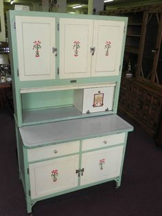 Mint green Hoosier cabinet with white doors and a simple flowered applique