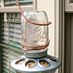 A backyard bird feeder is a fun way to enjoy wildlife, and Vicki and Jennifer of 2 Bees in a Pod have a quick and easy way to bring feathered friends flocking. Simply screw a galvanized chicken feeder to the top of a Mason jar filled with a birdseed blend, then wrap thick-gauge copper wire around the jar, leaving plenty of room for a hanger. In less than 5 minutes, you've created the perfect hangout for hungry birds!/