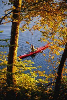 'National Geographic: Woman kayaking with fall foliage, Potomac River, Maryland.'