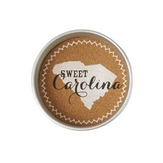 Set of 4. Galvanized metal jar lids feature state print and sentiment on cork centers. Coasters come stacked and tied for gifting.