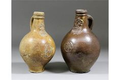 Two 17th Century brown salt glazed stoneware Bellarmine jugs one with applied mask and seal of tw