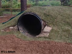 Mole hill natural play space with tunnel, slide, and porthole at prairie ridge ecostation