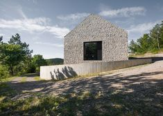Rural Slovenian cottage featuring walls of stone set into concrete.