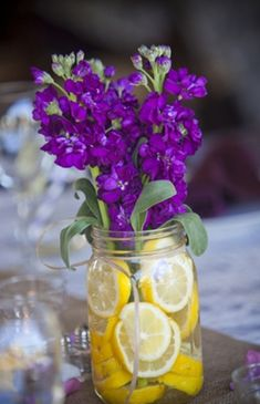 Pretty in Purple and Yellow Wedding Colors - love the Mason jars!  Simple and pretty.  I used fruit (whole lemons too) in my wedding flower arrangements and got so many compliments. #dphiewedding #purplewedding
