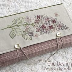 """Sweet Lilacs ~ book wrap"" pattern by Melissa Grant of One Day in May. A embroidered, lilac themed book wrap for wrapping and protecting a book or journal for travel or for safekeeping."