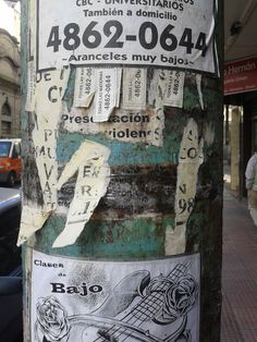 Typical lamppole in Buenos Aires used by individuals to offer their services.