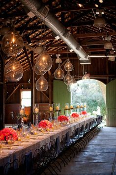 Modern versus rustic! This barn wedding reception sets the mood for a rustic evening, add in the hanging clear globes with lit candles, simple centerpieces with raised candle vases creates a modern mix that gives this setting the perfect balance! Don't be afraid to mix things up and combine different styles and themes--you may be surprised how well certain pairings work together.