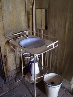 Lavabo del palazzo Lauria en San Mauro Forte - Italia. Un eficiente diseño de la década de 1930, con el cepillo de la crema de afeitar intacta. A su lado está el cubo de la noche, el predecesor del cuarto de baño.