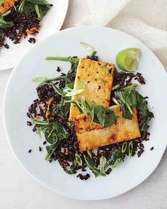 Fried Black Rice With Ginger Tofu and Spinach Recipe: Bring rice and water to a boil in a small saucepan. Reduce to a simmer, cover, and cook until rice is tender and liquid is absorbed, about 45 minutes. Let stand 5 minutes. Fluff with a fork and set aside. Steam spinach, covered, in 1 tablespoon oil over medium-high heat for 2 minutes; set aside. Saute garlic, ginger, and scallion whites in remaining oil until fragrant, about 1 minute. Add tofu and Sriracha and cook until tofu is golden, about 6 minutes per side. Remove and set aside. Add rice to skillet and cook over medium-high heat until crisp, about 2 minutes. Serve with spinach and tofu. Garnish with scallion greens and serve with lime.