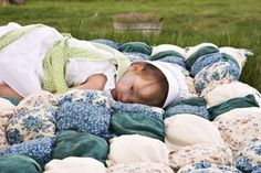 Amish Child Lying Outdoors On A Handmade Biscuit Quilt