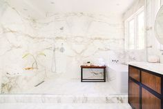 All marble bathroom with wood cabinets and large bathtub