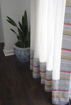 I think I could make these...use sheer curtains that are more inexpensive and then pick a decorator's fabric in a smaller amount to use as the trim.  Very pretty!