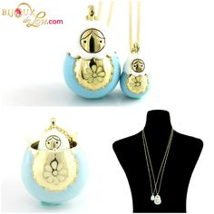 Blue Enameled Matryoshka Necklace Set: Each set consists of a mother locket on a long gold plated chain & a baby doll pendant on a long gold plated chain. The mother locket is around 1 3/8 inches high while the baby is 5/8 inch high. The pendants are made of gold plated brass and then hand painted in blue enamel.