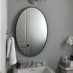 Looking to open up space in your well-appointed master suite? This sleek beveled oval wall mirror brings function and flair to your favorite aesthetic. Play up this piece's versatility by adding it to a contemporary restful retreat alongside a gently arched headboard for visual appeal. Round out the room with a streamlined side chair, perfect paired with a burlap pillow for an unexpected touch of farmhouse flair, then drape a cable-knit throw over its back for a casual look. Dot nearby wa...