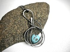 This silver wire wrapped pendant has a unique, modern design that really stands out from the crowd. I hand forged the framework of the pendant out of fine silver wire. Hammering the wire gave it added texture and character. Then I used additional smaller gauge fine silver wire to hand craft wire wrapped details that bring the design together and frame the turquoise colored natural stone bead that is the focal point of this pendant. The last step was to oxidize the silver and then hand polish…