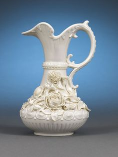 This magnificent porcelain jug was crafted by the famed Belleek firm of Ireland. Known as an Aberdeen jug, this vessel is a stunning example of Belleek's renowned attention to detail. Boasting a split, scrolling handle and lush, ruffled spout, the jug's exuberant design is distinguished by the hand-crafted, lifelike flowers applied to its full body.Known for being extremely dainty and lightweight, Belleek porcelain is among the finest in the world. Distinguished by designs tak…