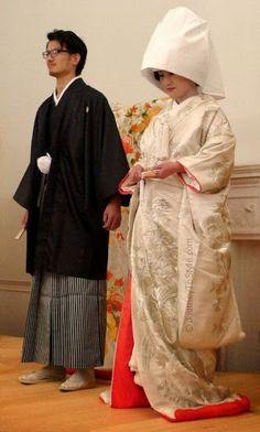 The traditional Japanese wedding costumes of 'montsuki' kimono, hakama and haori (for the groom), and white 'shiromuku uchikake' and kimono (for the bride).