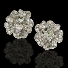 Elegant pair of naturalistic earclips each designed as a flowerhead cluster with diamond-set petals around cushion-cut diamond centres, mounted in platinum, Cartier, London c1930