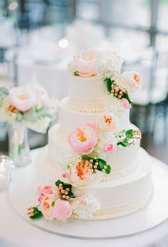 A colorful four-tiered wedding cake with cascading garden roses, peonies, hydrangea, and berries, created by Cravings.