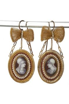 Gold earrings with pendant plaques enamelled en camaieu with classical heads in profile. Each plaque is bordered with pearls and suspended by three gold chains from a gold bow. French c1805. Museum of London