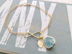 A 14k gold filled double strand infinity bracelet with a cracked aquamarine glass gemstone and one hand stamped leaf initial charm. Available in 14k