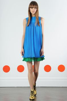 This dress has a distinct 1960s inspiration. The bright colors and contrast indicate the time period. The mod, shapeless design, as made famous by Twiggy, is clear in this design.