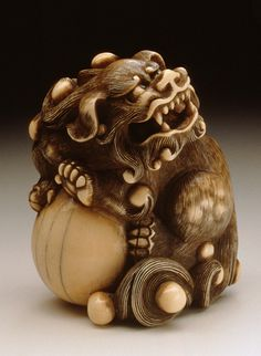 Chinese Lion Guarding the Jewel of the Buddha, 18th century  Netsuke, Ivory with staining, sumi, inlays