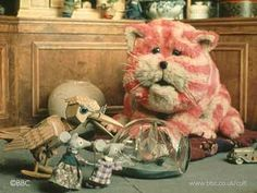 Bagpuss .... And so their work was done. Bagpuss gave a big yawn and settled down to sleep. And, of course, when Bagpuss goes to sleep, All his friends go to sleep too. The mice were ornaments on the mouse organ. Gabriel and Madeleine were just dolls. Professor Yaffle was a carved, wooden bookend in the shape of a woodpecker. Even Bagpuss himself, once he was asleep, was just an old, saggy cloth cat, Baggy, and a bit loose at the seams, But Emily loved him .... and so did I !!