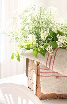 linen teatowels lining flower-filled basket for a fresh summer look