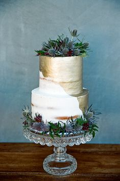 Amazing, creative half-naked, half-gold dipped wedding cake, topped with thistles.