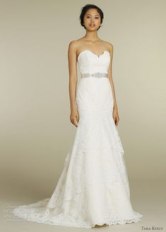 Alencon lace bridal gown with elongated bodice and scalloped tiered skirt, strapless sweetheart neckline, satin ribbon belt with beaded applique at natural waist and chapel train.