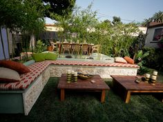 This backyard is a Balinese paradise with an outdoor lounge area and dining area. Two low tables sit in front of a sectional bench, providing a place to relax with family and friends.