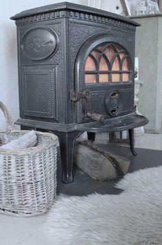 vintage houtkachel met klassieke details en een heeeeele dunne plaat eronder