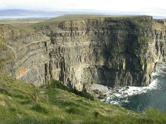 The Cliffs of Moher (Irish: Aillte an Mhothair) are located at the southwestern edge of the Burren region in County Clare, Ireland. They rise 120 metres (390 ft) above the Atlantic Ocean at Hag's Head, and reach their maximum height of 214 metres (702 ft) just north of O'Brien's Tower, eight kilometres to the north. The cliffs receive almost one million visitors a year.