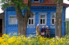 [RUSSIA.GOLDENRING 26.021]  'Exchanging gossip.'    Neighbours are exchanging gossip in front of an izba (traditional wooden house) in Ves village, north of Suzdal. Photo Mick Palarczyk.