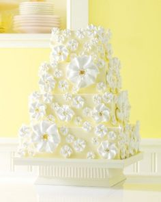 A stunning yellow wedding cake blooming with flowers