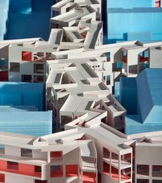 """""""Architectural model of MOS's Thoughts on a Walking City project for Orange, New Jersey, showing the proposed mixed-use development in white filling the street spaces between the existing buildings in blue"""", by MOS architects"""
