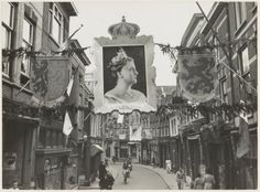 1948, Kleine Houtstraat bij de hoek Helmbrekerssteeg ziende naar het zuiden. De straat is versierd ter gelegenheid van het 50-jarig regerings jubileum van Koningin Wilhelmina.