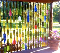 DIY Wine Bottle Fence. Use a diamond drill to make holes in the bottles and thread them on poles.