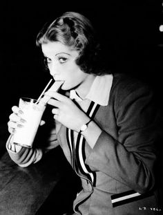 Lucille Ball blowing bubbles in her beverage through a straw on June 8, 1938