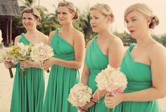 These Langkawi bridesmaids dress up a beach wedding with modern cuts and necklines in their emerald green flowing dresses by twobirds.