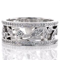 Micro pavé diamonds frame the naturalistic arrangement down the center of the band. The outline of the vine is decorated with leaves and circular patterns. Each leaf and circle features round brilliant diamonds for sparkle and fire. Milgrain texture adds dimension to all the outside edges.