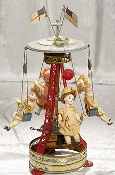 19 Inch German painted tin mechanical whirl-a-gig with four bisque dolls.jpg