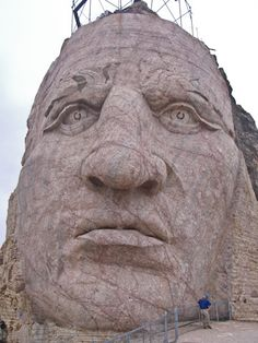 Crazy Horse Memorial: A man stands next to the face of the Crazy Horse Memorial