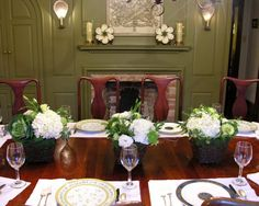 Green and white botanical centerpieces in twig and moss baskets coordinate with interiors for a spring dinner party.