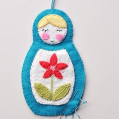 #8   Matryoshka Doll Ornament  Secure string or ribbon hanger on the inside center of the back piece with a glob of fabric glue. Once dried, place front & back pieces together with right sides facing out. Blanket stitch around edge leaving a space big enough to add stuffing through.