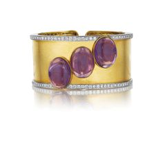 DAVID WEBB, An Amethyst, Diamond and Gold Cuff Bracelet - Designed as a wide textured yellow gold hinged cuff, set with three oval cabochon amethysts, to the circular-cut diamond border, mounted in 18K yellow gold.