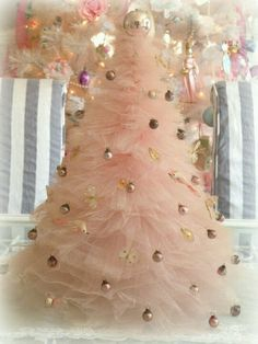 I used to have a pink nylon net & tulle tree like this made with gathered rings of tulle and net stacked on a dowel on a plywood base. It lasted for years!